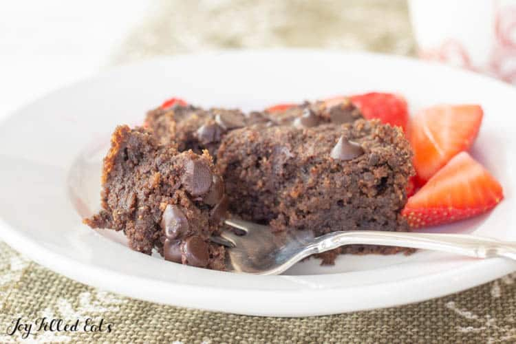 low carb brownie on a plate with small bite broken off on fork. Plate also includes a side of cut strawberries