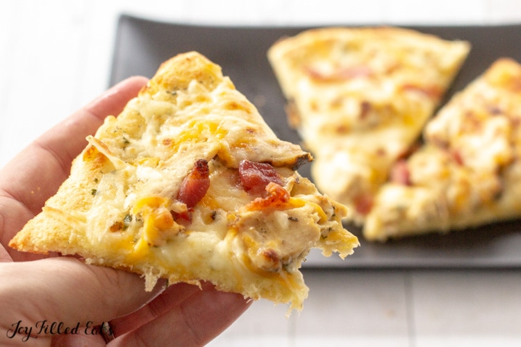 hand holding up a slice of keto Chicken Bacon Ranch Pizza
