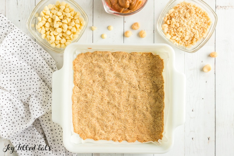 baked caramel magic cookie bar crust in square white baking dish. white chocolate chips in separate small mixing dish. Chopped macademia nuts in separate small mixing dish.