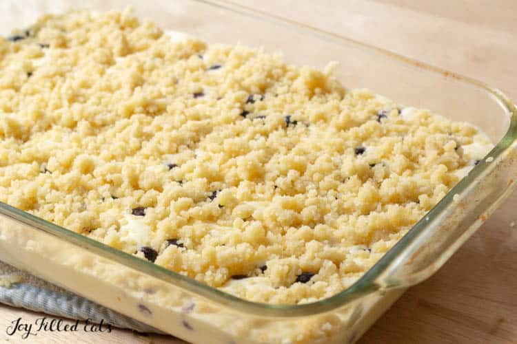 baking dish of batter with crumb topping for lemon blueberry cheesecake crumb bars