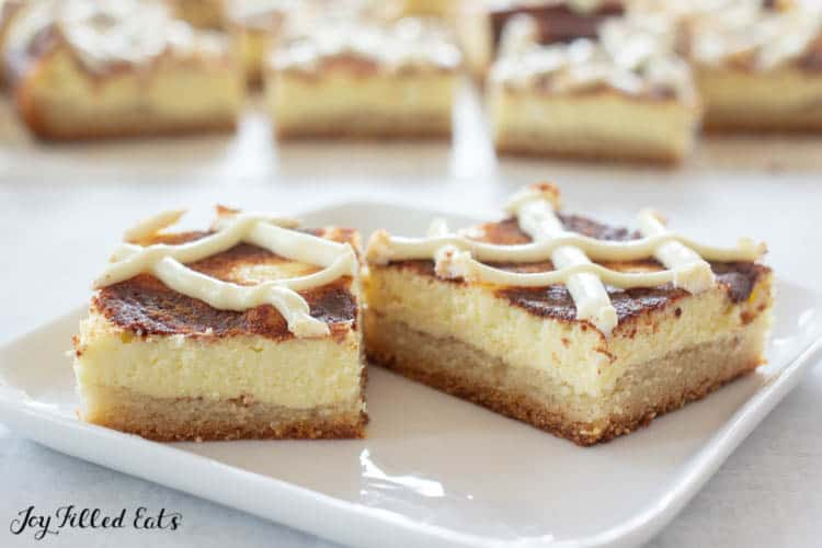 White plate of two square cinnamon bun cheesescake bars with other square slices in background