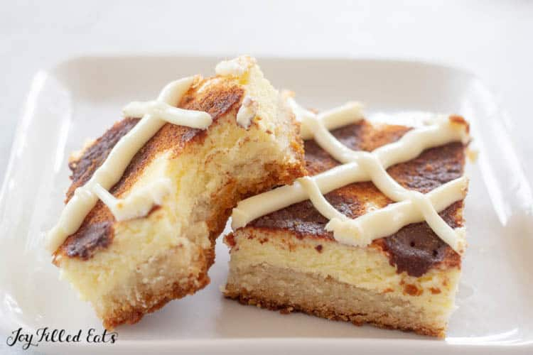 two cinnamon roll cheesecake bars on white plate with bite missing from one.