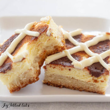 two cinnamon roll cheesecake bars on white plate with bite missing from one