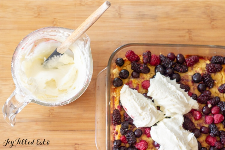 mixed berry cake being topped with cream cheese icing