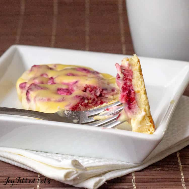 Raspberry Cream Cheese Danish on white plate. Piece broken off onto fork.