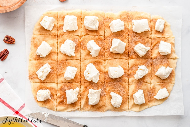 dough cut into squares topped with cubes of cream cheese