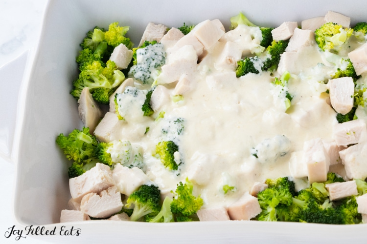 alfredo sauce on top of chicken and broccoli in a casserole dish
