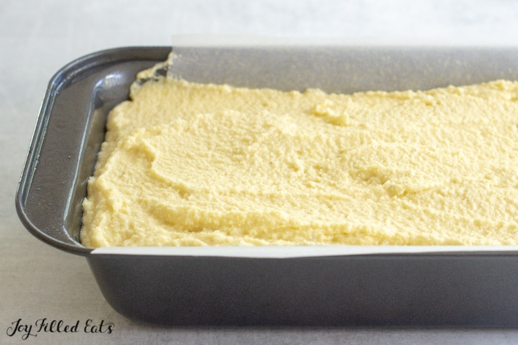 keto lemon pound cake batter formed into parchment lined bread pan