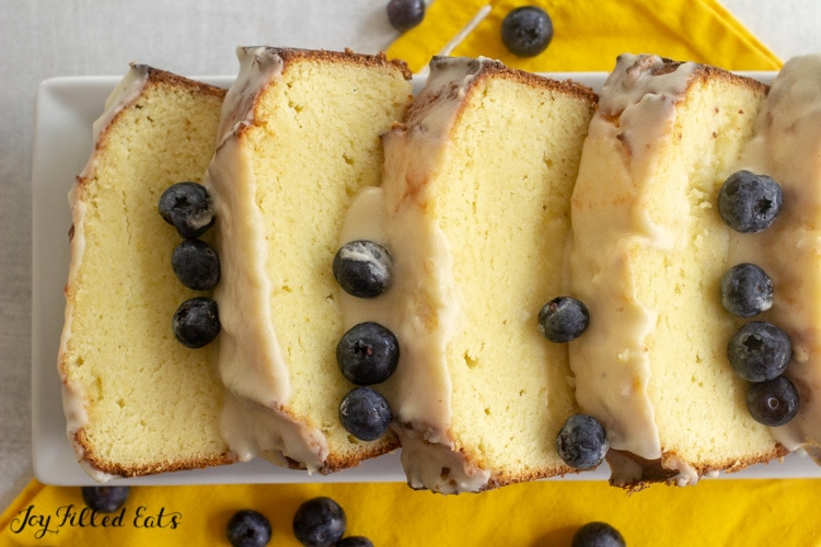 keto lemon pound cake slices topped with a glazed icing and blueberries fanned out on a white platter