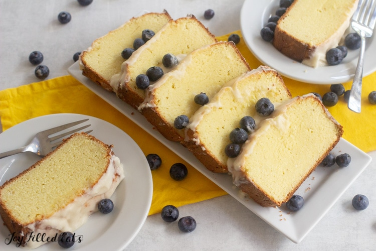 white rectangular platter of keto lemon pound cake slices topped with icing and blueberries next to two plates, each with a slice of pound cake and fork