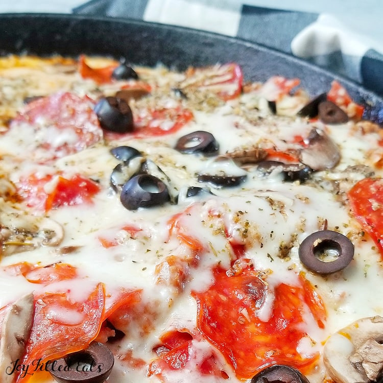 skillet meatzza with cheese and olives close up