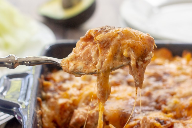 close up of spoon scooping a serving of Mexican Chicken casserole from the dish with cheese strings dripping off spoon