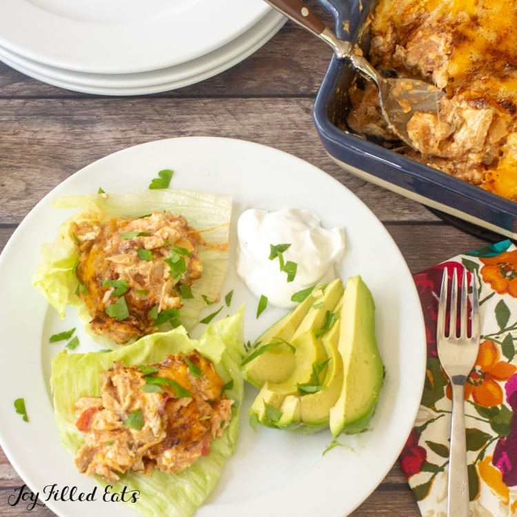 plate of Mexican chicken casserole servings on lettuce leafs next to sliced avocado and a dollop of sour cream from above. plate is set next to a fork and decorative napkin, stack of plates and casserole dish with spoon.