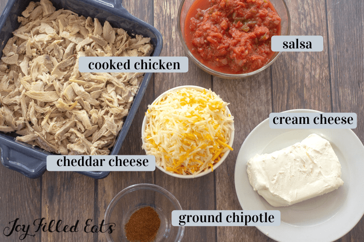 individual ingredients including cooked chicken in a casserole dish, shredded cheddar cheese, salsa, cream cheese and ground chipotle