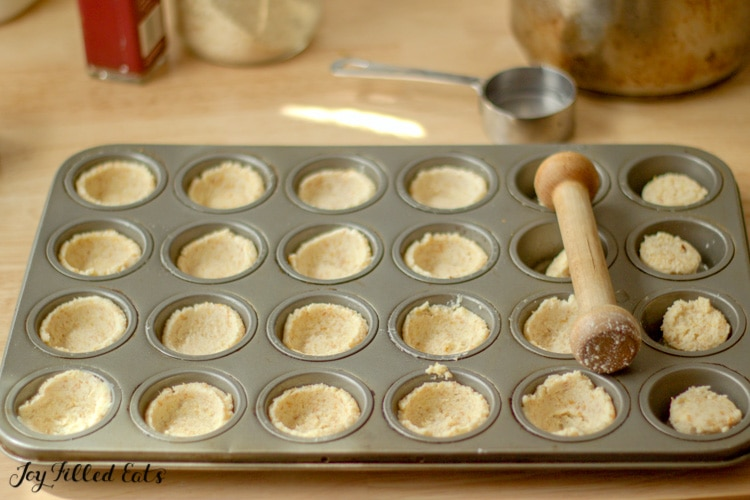 dough pressed into a mini muffin tin