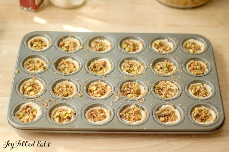nuts inside cookie dough cups in a mini muffin pan
