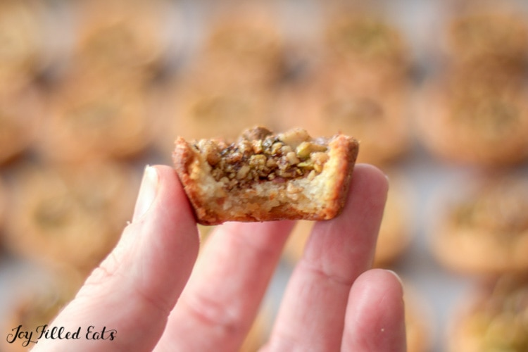 hand holding a baklava cookie with a large bite missing