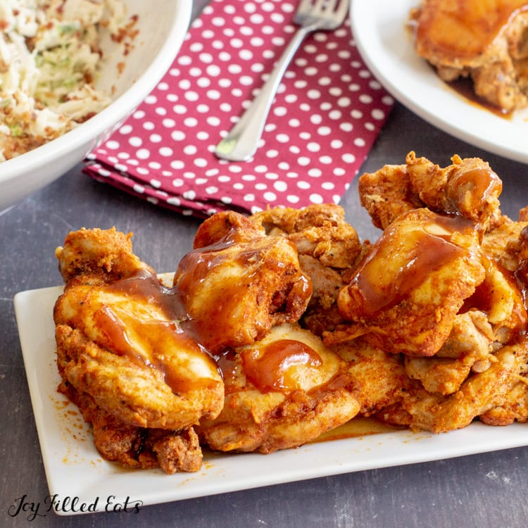 white platter piled high with bbq chicken thighs