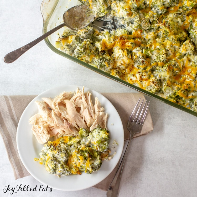 keto broccoli casserole in a glass baking dish and on a plate with chicken