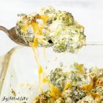 a spoon lifting up broccoli with melted cheese