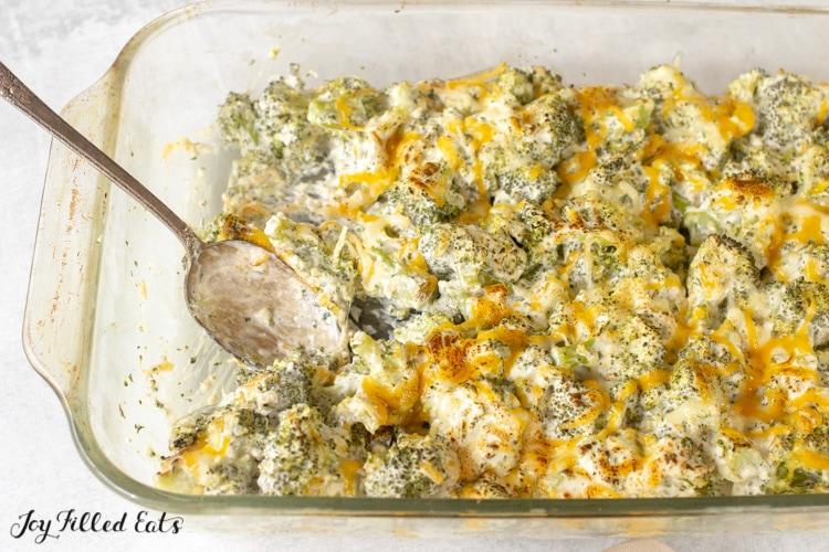 a spoon in a casserole dish with keto broccoli casserole