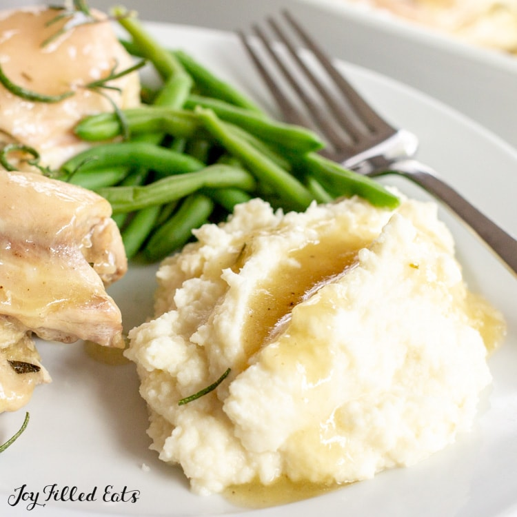 a plate with chicken, green beans, and keto cauliflower mash with gravy