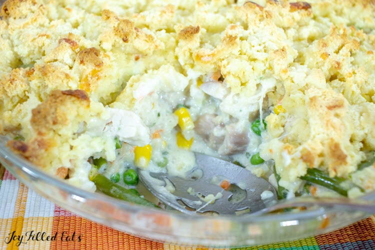 close up on low carb chicken pot pie with biscuit topping with slice missing