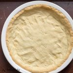 close up on overhead view of low carb pie crust baked into white pie plate with fork holes punched in