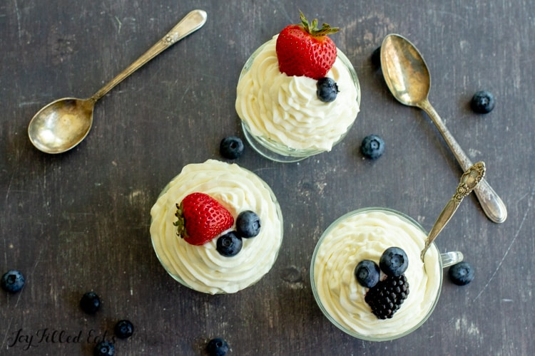 three bowls of keto cheesecake fluff topped with berries