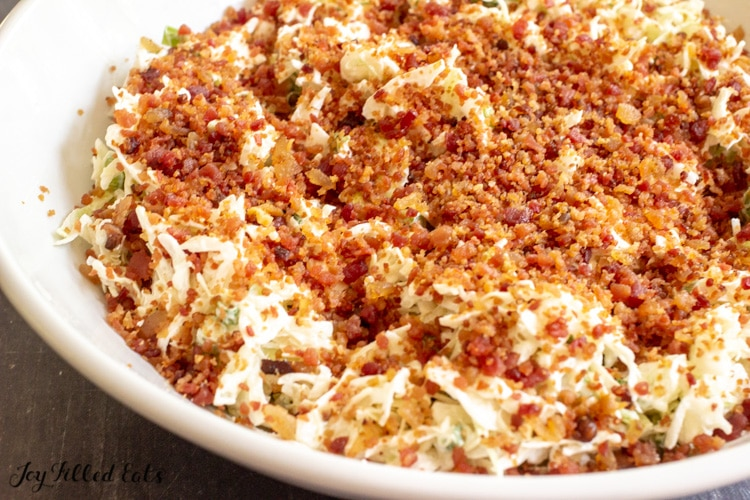 keto coleslaw topped with bacon crumbles in a large bowl