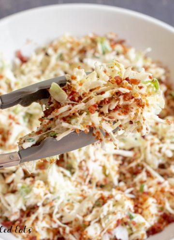 tongs lifting up some keto coleslaw from a large bowl