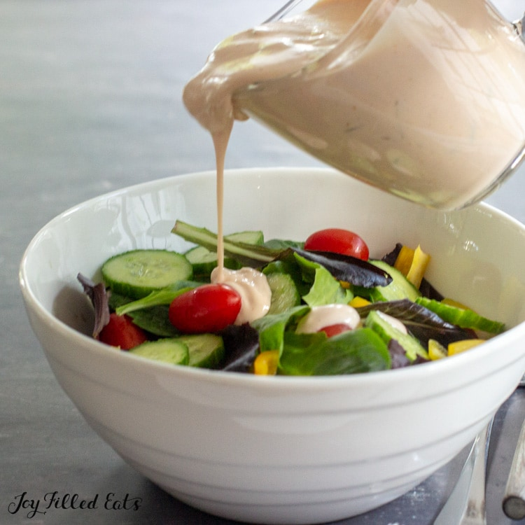 pitcher pouring keto thousand island dressing on top of a green salad in a white bowl