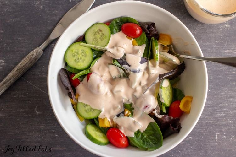 bowl of green salad with tomatoes and cucumbers