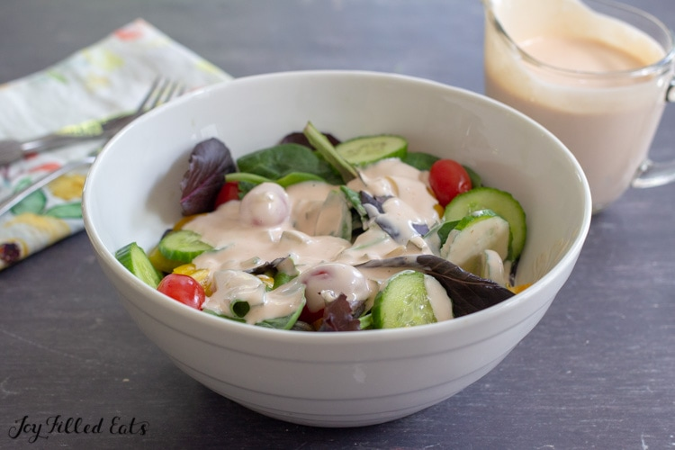 bowl of salad with a pitcher of keto thousand island dressing next to it