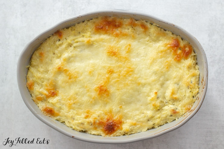 baking dish of twice baked spaghetti squash with melted browned cheese on top