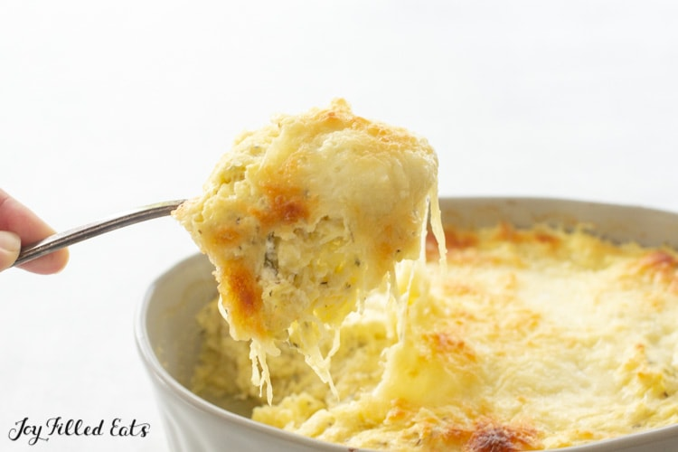 a spoon lifting up some keto spaghetti squash casserole with melted cheese