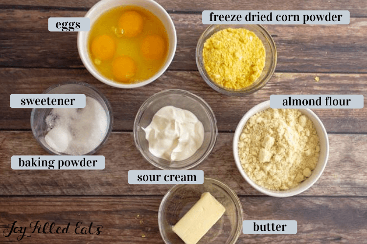 ingredients in small bowls including almond flour, eggs, sour cream, butter, and freeze dried corm