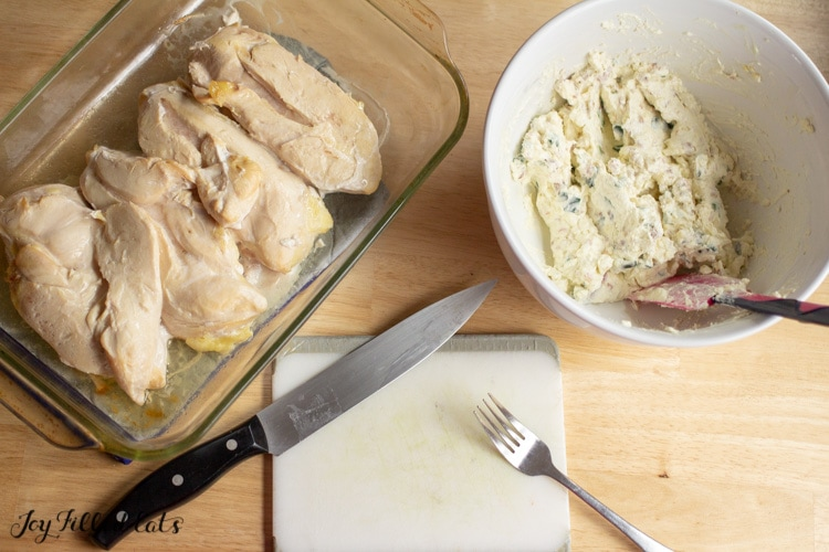 chicken placed in a casserole dish next to a mixing bowl of jalapeno popper dip and cutting board with a fork and large knife