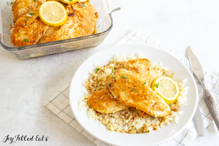 two pieces of chicken on top of cauliflower rice in a shallow bowl with a lemon slice