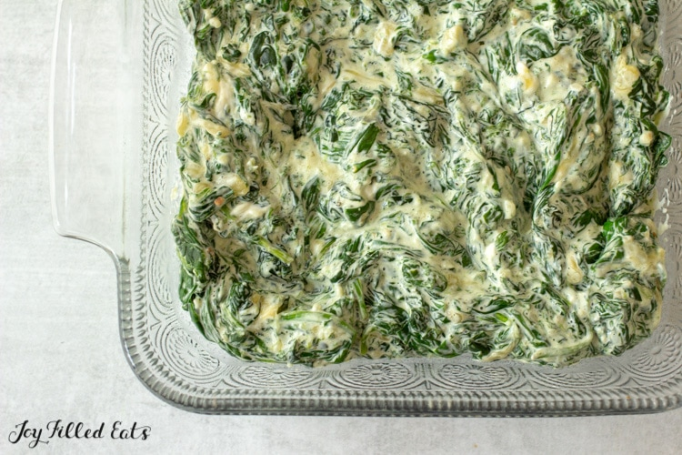close up on casserole dish full of creamed spinach