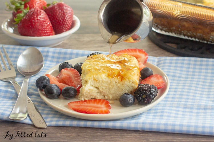 a hand pouring syrup over the keto dutch baby on a plate with berries