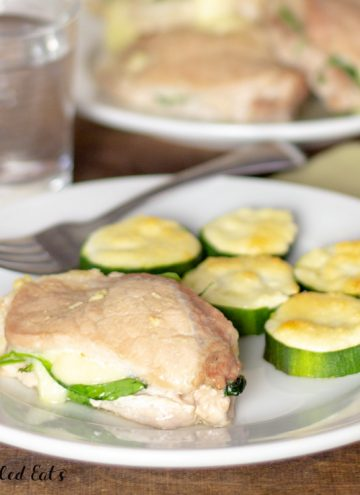 one of the keto pork chops on a plate with zucchini, more in the background