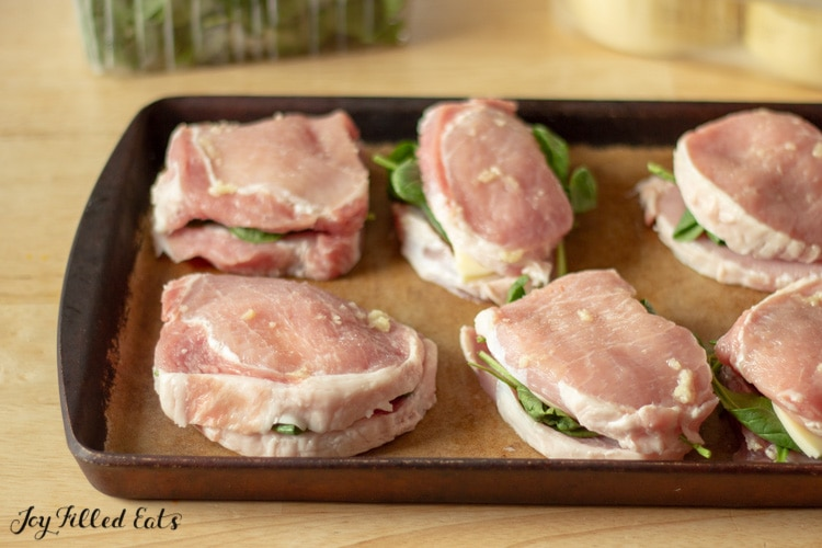 keto pork chops on a baking dish stuffed with spinach