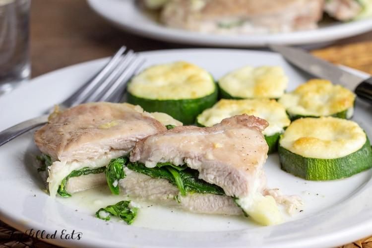stuffed pork chop cut in half on a plate with zucchini