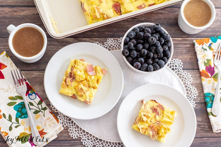 overhead shot of the keto eggs benedict casserole in a baking dish with pieces on two plates, coffee, and blueberries