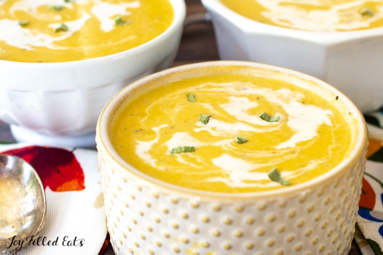 close up of a bowl of low carb butternut squash soup with swirls of cream and chopped sage
