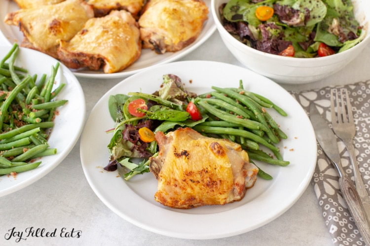 a cooked chicken thigh on a plate with salad and green beans