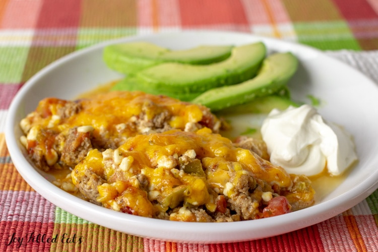Easy Keto Taco Casserole Recipe served on a white plate with sliced avocado and sour cream