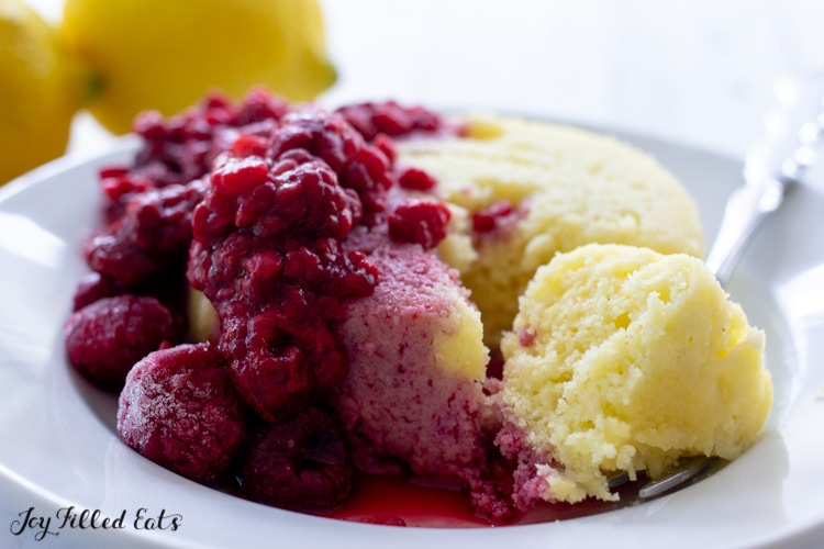 lemon mug cake with thawed frozen raspberries and the juice soaking into the cake
