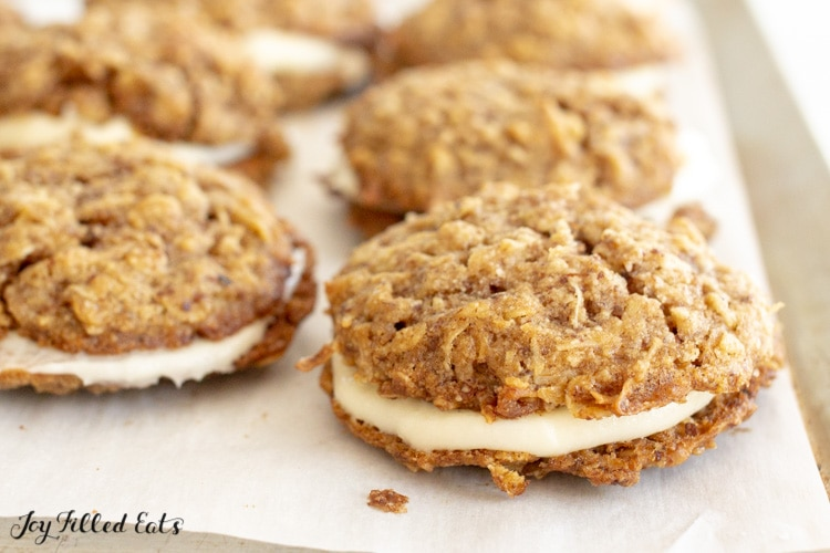 a baking sheet lined with parchment with keto oatmeal cream pies sandwiched with creamy filling